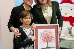 Η μικρή Γεωργία μαζί με τη Διευθύντρια της Μονάδας Μεταμόσχευσης Μυελού των Οστών κυρία Βασιλική Κίτρα προσφέρουν στην Μαριάννα Β. Βαρδινογιάννη έναν πίνακα ζωγραφικής που έφτιαξαν της Μονάδας Μεταμόσχευσης Μυελού των Οστών