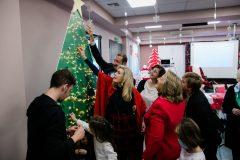 Οι κυρίες Βαρδινογιάννη και Παυλοπούλου τοποθετούν στολίδια που έφτιαξαν τα παιδιά στο χριστουγεννιάτικο δέντρο